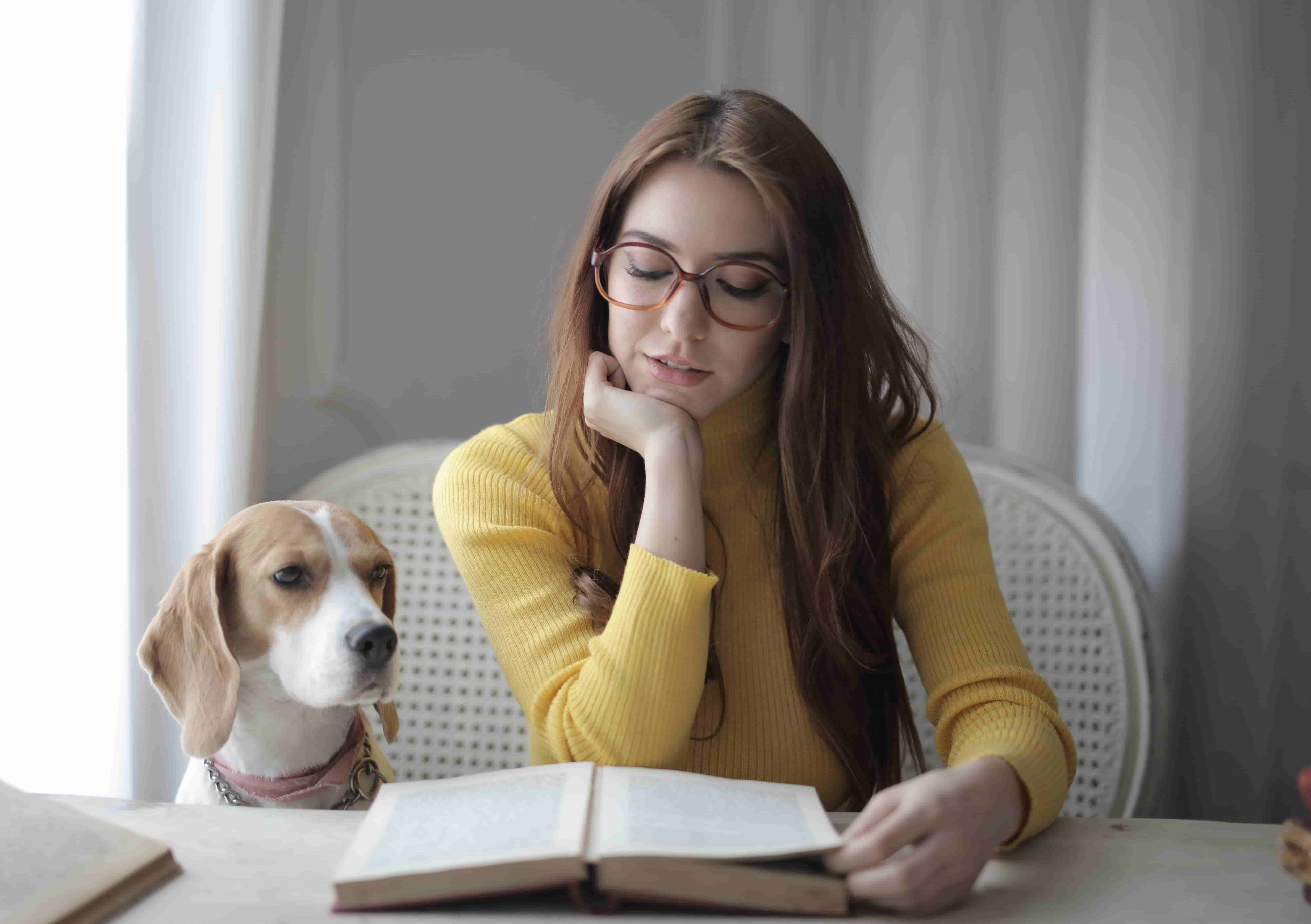 Girl with prescription glasses is reading a book