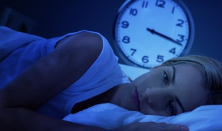 woman having difficulties falling asleep with blue light